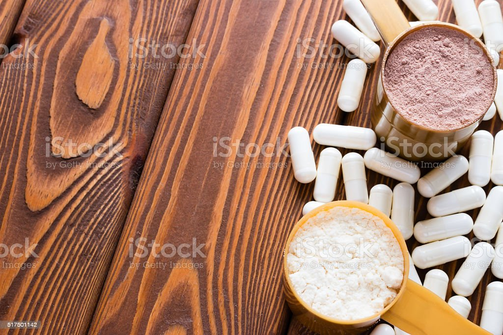 capsules of creatine and protein measuring spoons closeup stock photo