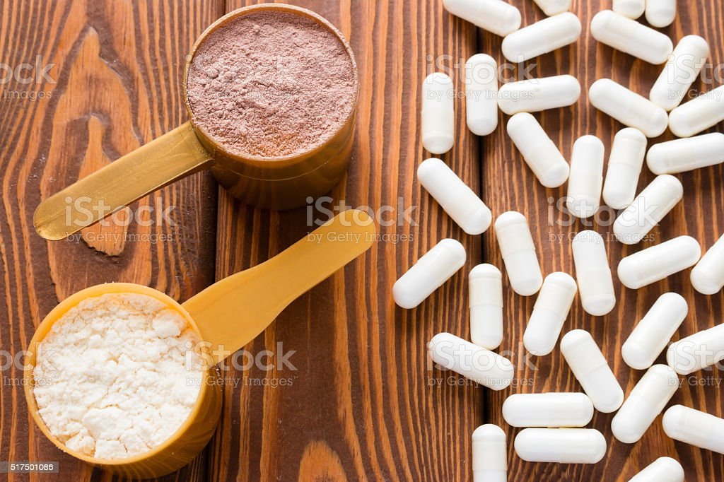 capsules of creatine and protein measuring spoons stock photo