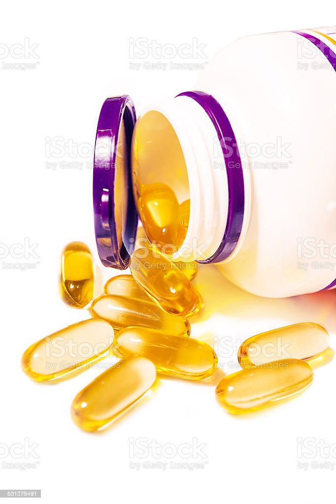 Capsules spilled from pill bottle stock photo