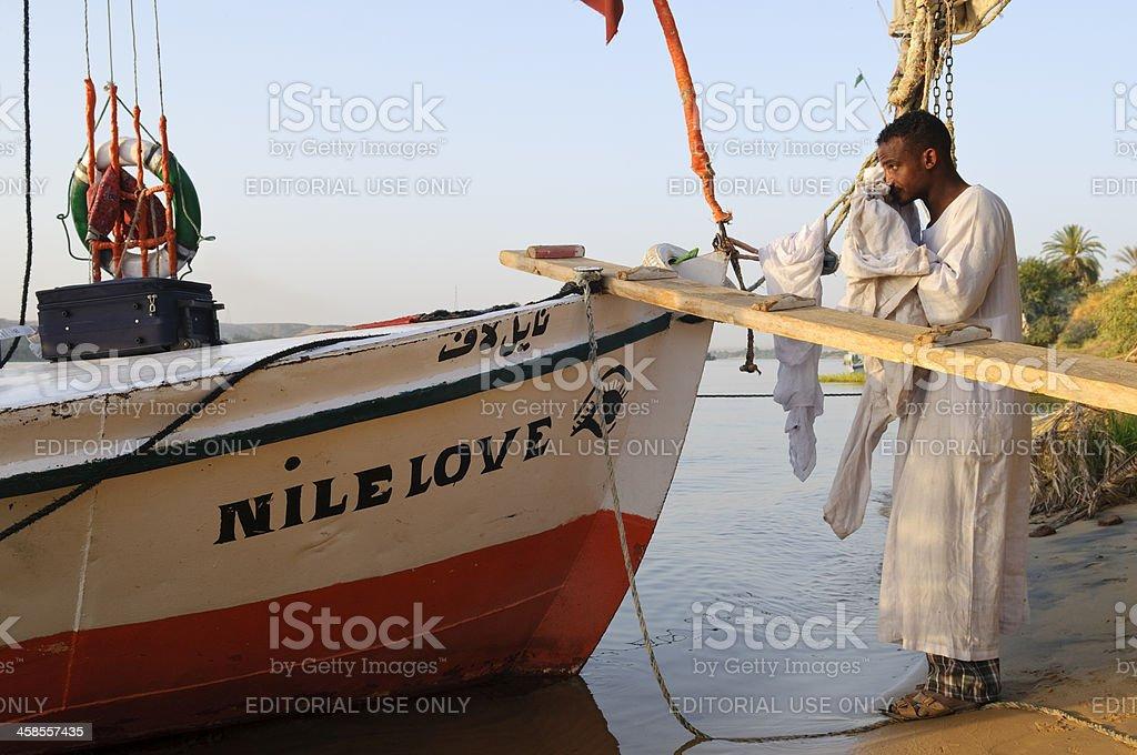 Captain and his felucca on the Nile River royalty-free stock photo
