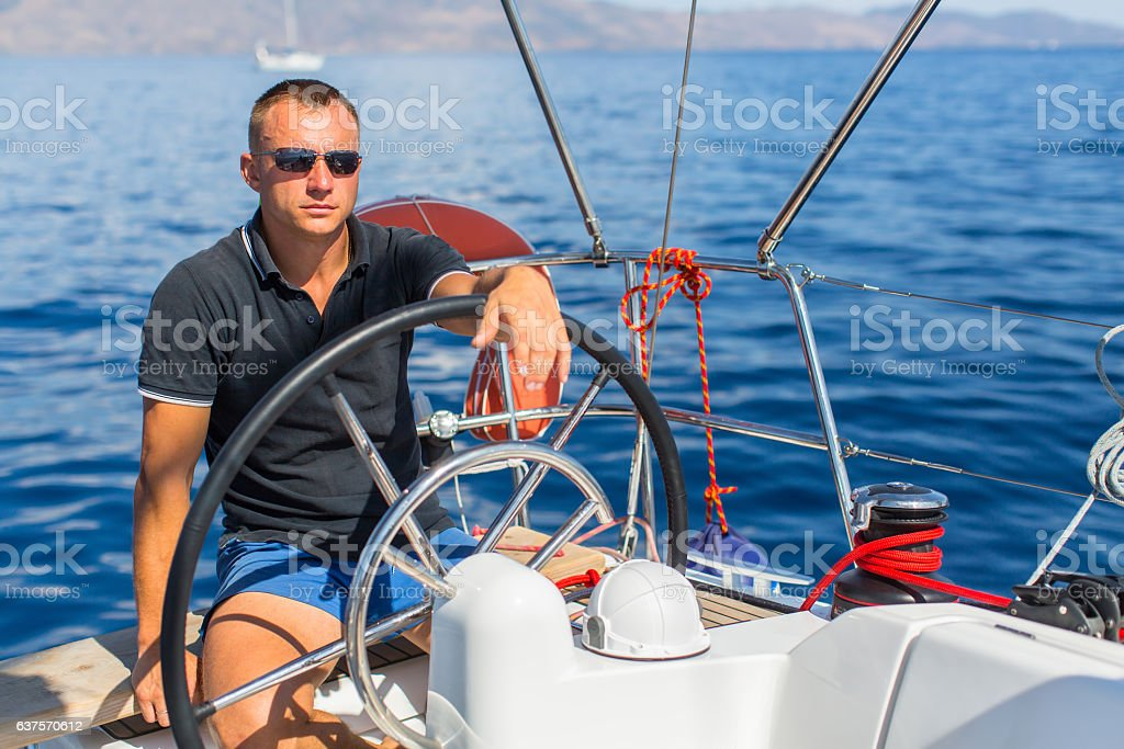 Captain at the helm controls of a sailing boat stock photo