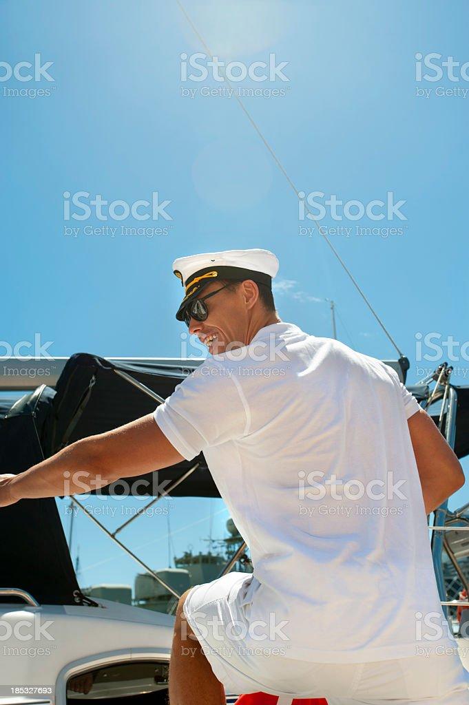 Captain boarding a sail boat stock photo