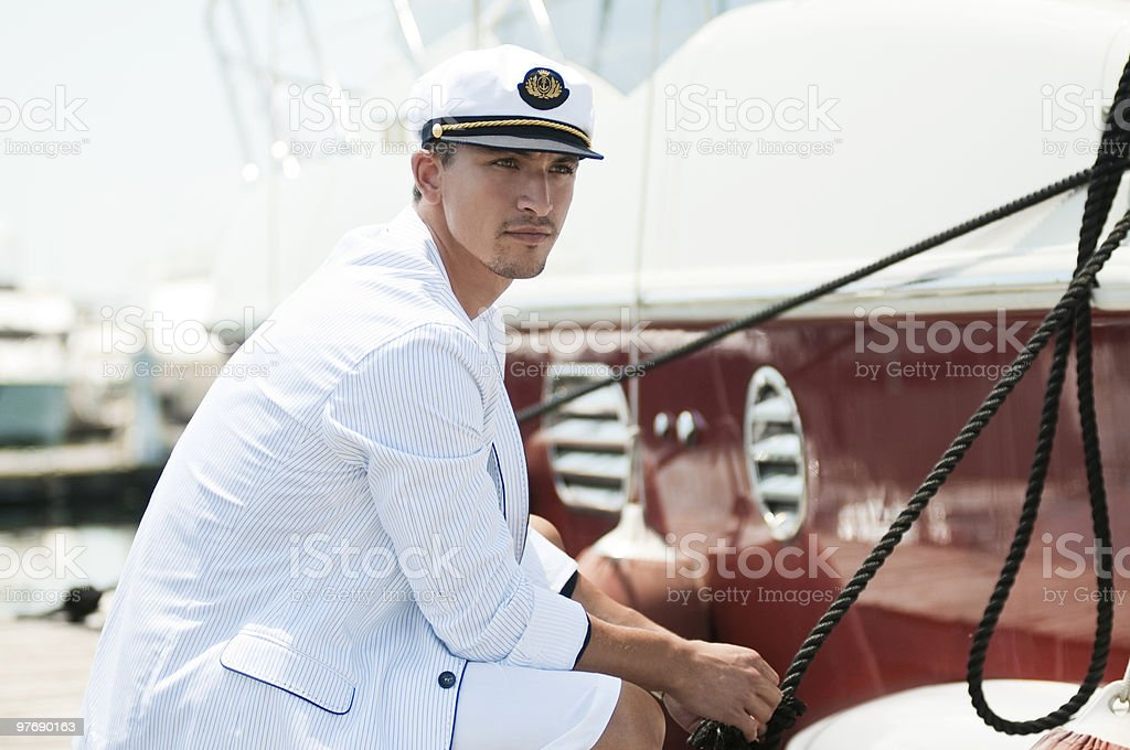 captain holding rope of the yacht stock photo