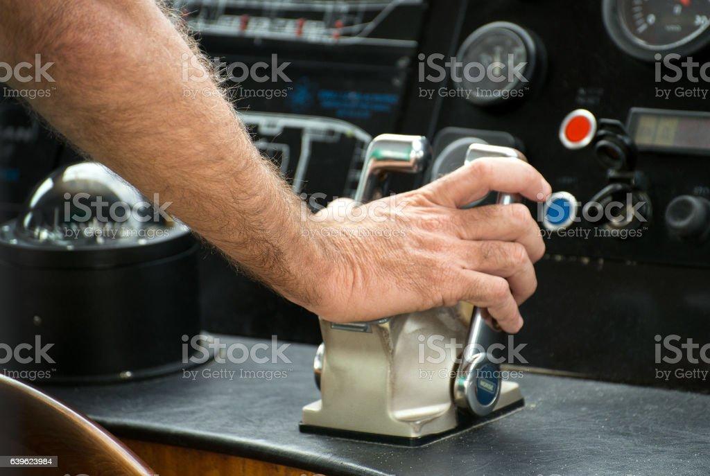Captain's hand on ship throttle. stock photo