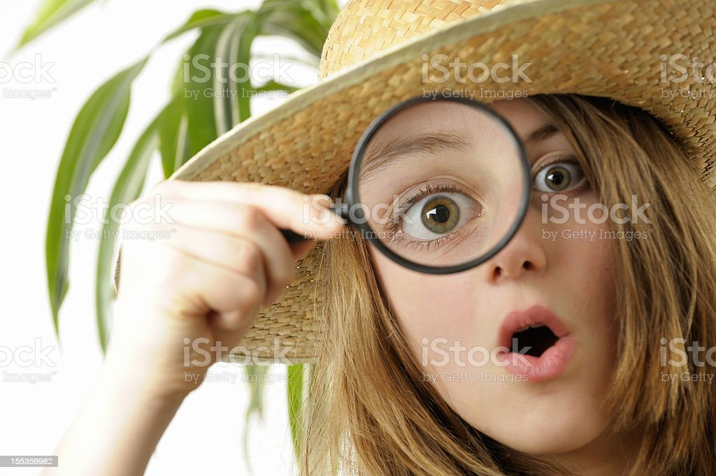 Captivated girl looks through magnifier royalty-free stock photo