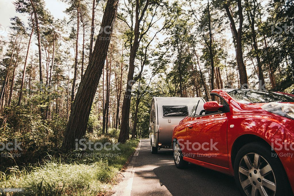 Car and caravan driving on forrest road in germany stock photo
