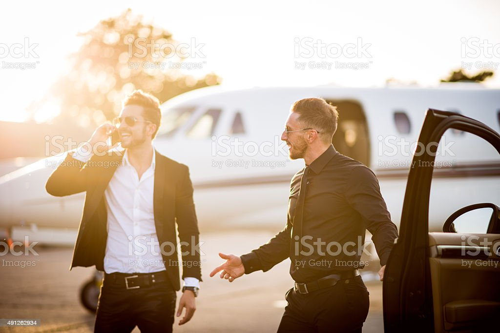 Young man with sunglasses dressed in black standing next to car and...