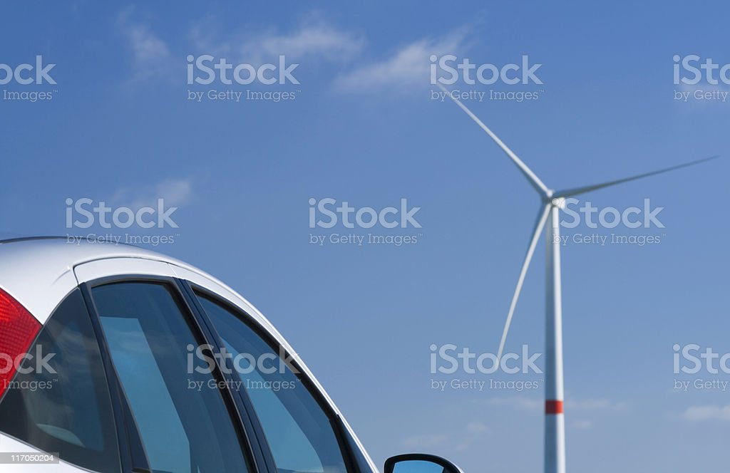 car and windmill stock photo