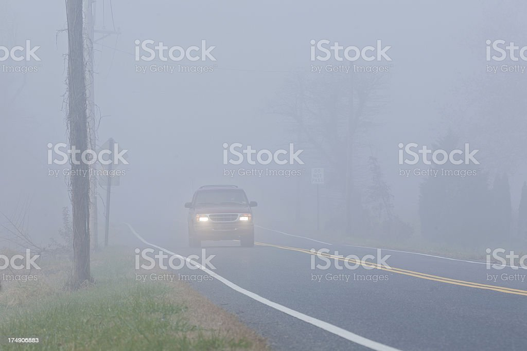 Car appearing through the fog with headlights on stock photo