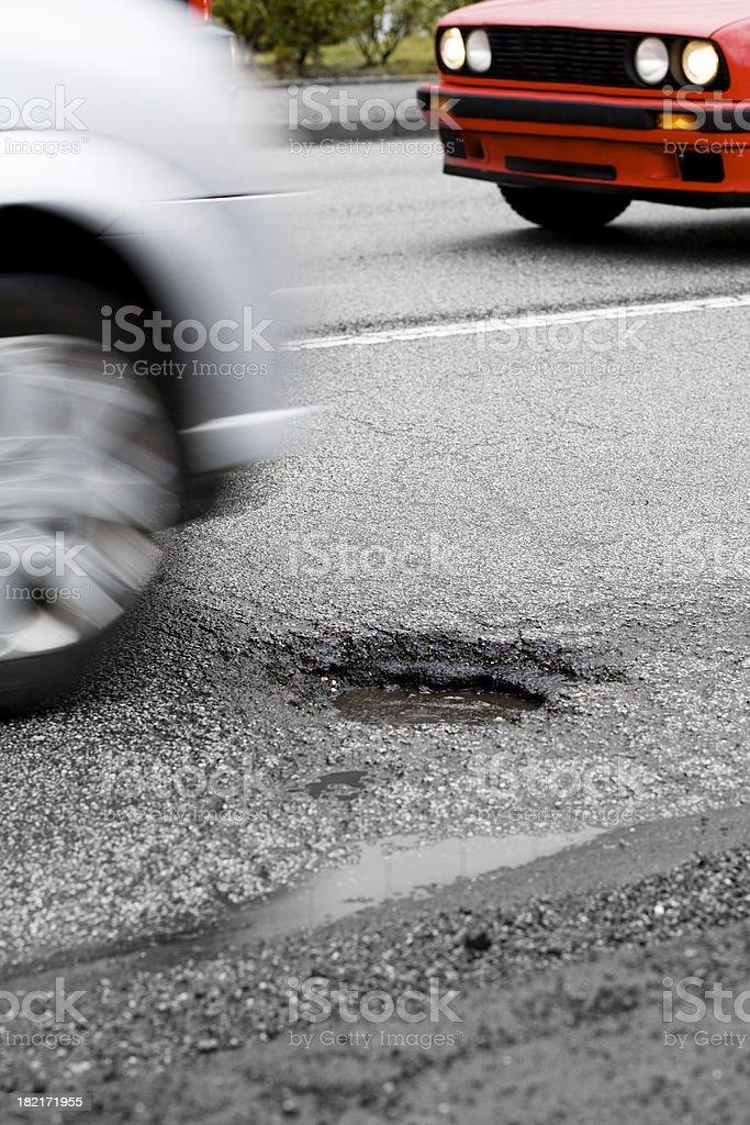 Car approaches a pot hole stock photo