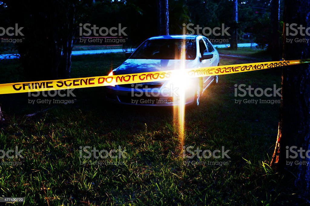 Car at crime scene in wooded area at night stock photo