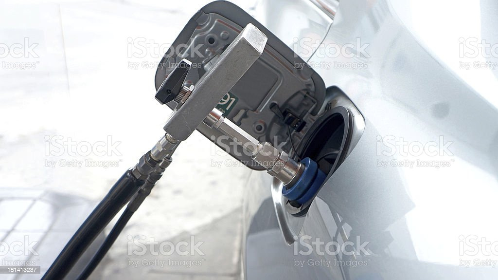 car at gas station being filled stock photo