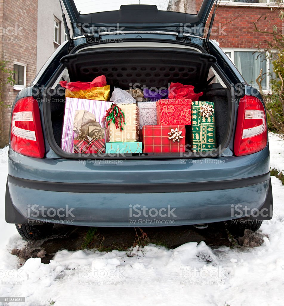 Car boot, filled with Christmas presents, snow underfoot stock photo