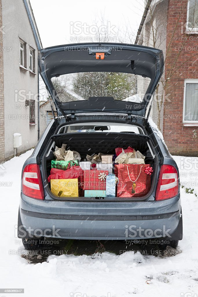 Car boot, filled with Christmas presents, snow underfoot; snowing stock photo
