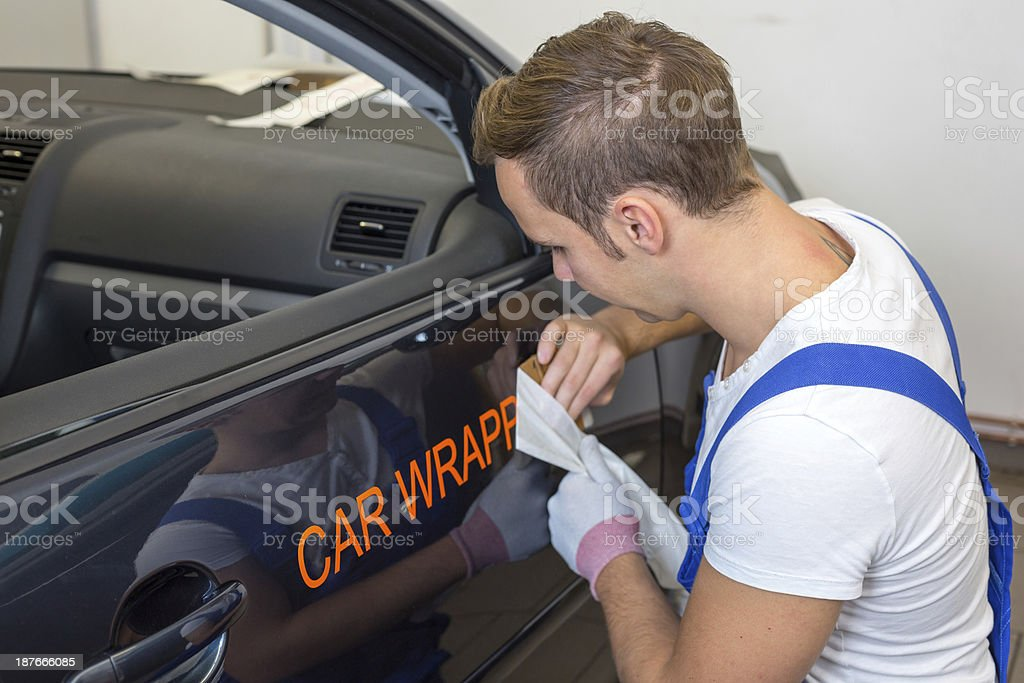 A car branding specialist applying a logo to a car stock photo