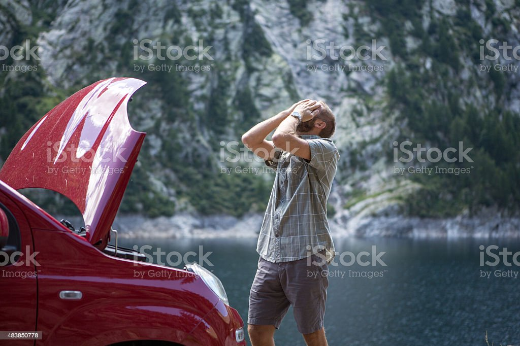 Car breakdown on mountain road. Frustrated young man stock photo