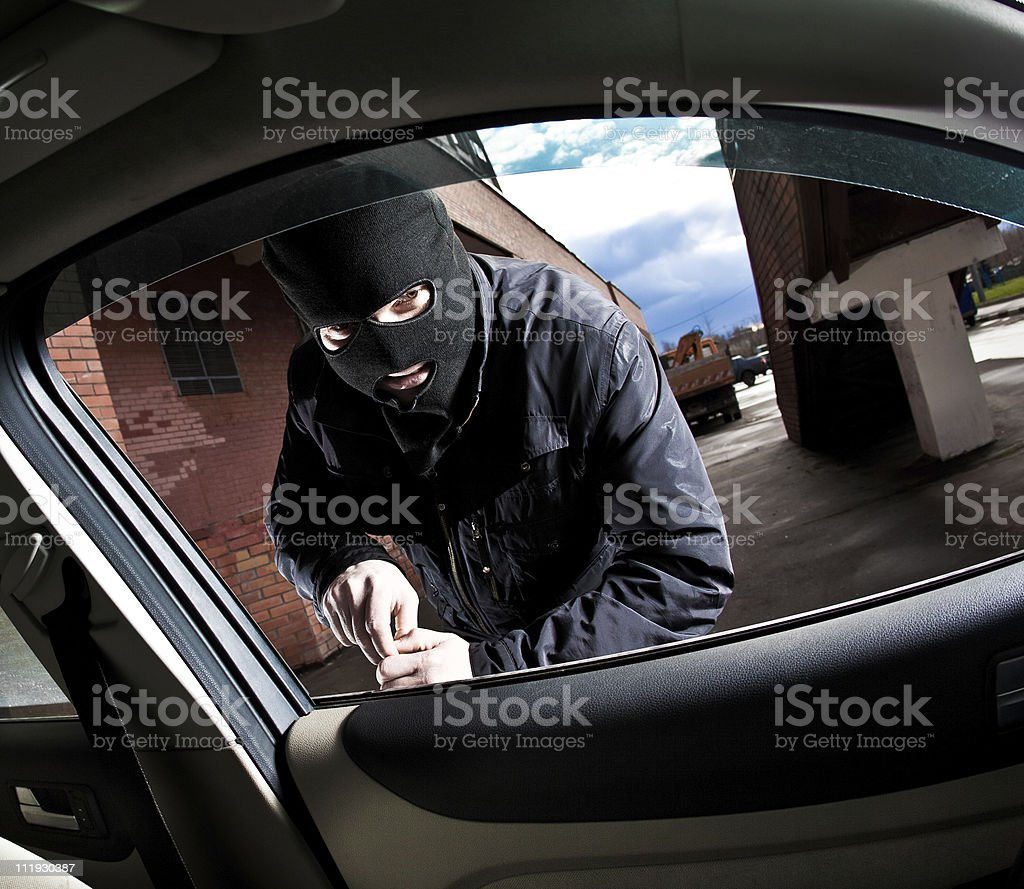 A car burglar attempting to break in royalty-free stock photo