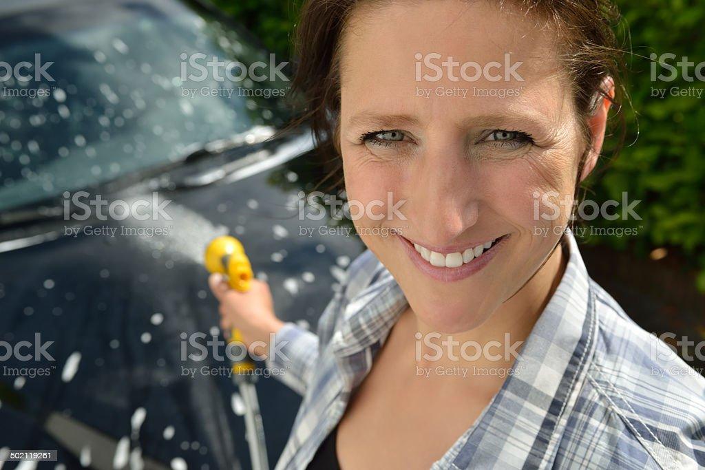 Car care - Woman using a garden spray gun stock photo