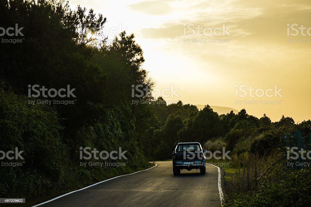 Car climbing the hills by dusk stock photo
