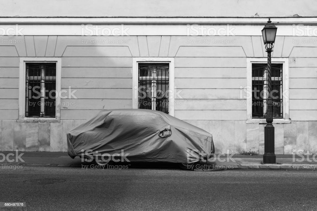 Car covered with textile cover in the street