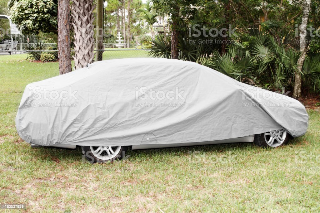 Car parked on lawn and covered with textile car cover to protect it...