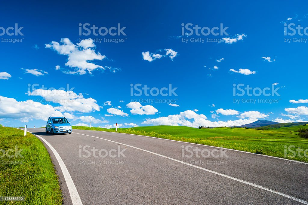Car crossing a country road in Tuscany stock photo