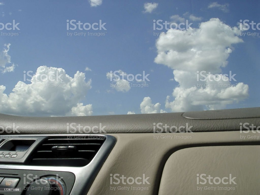 Car Dashboard and Puffy Clouds stock photo