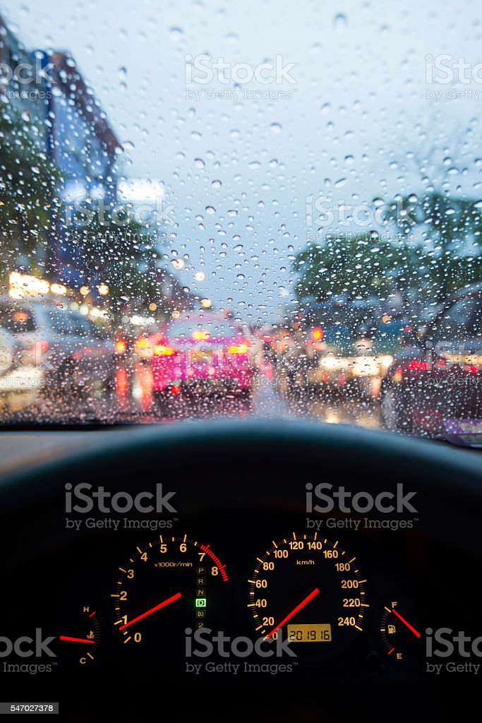 Car dashboard and wet windshield in a traffic in Bangkok stock photo