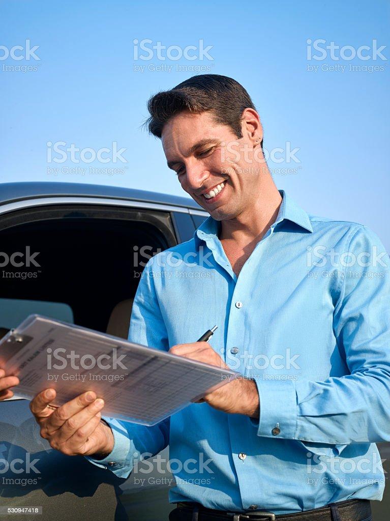 Car dealer giving key to man stock photo