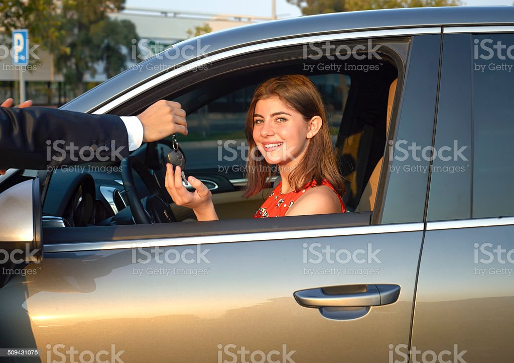 Car dealer giving key to young woman stock photo