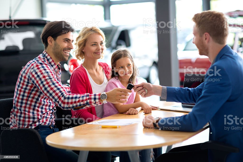car dealer selling new vehicle to young family stock photo