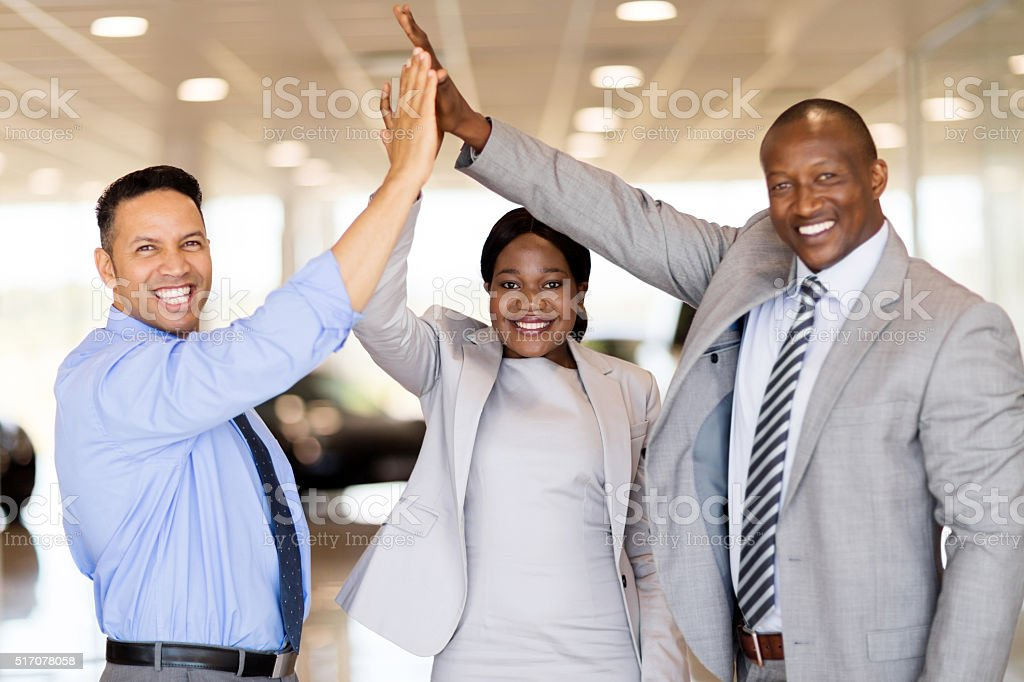 car dealership staff giving high five stock photo