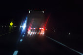 Car Driver POV Behind Lens Flare Illuminated Semi Trailer Truck