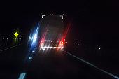 Car Driver POV Behind Lens Flare Illuminated Semi Trailer Truck
