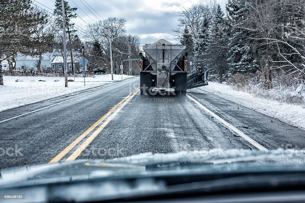 Car Driver POV Following Snowplow Spreading Road Rock Salt stock photo