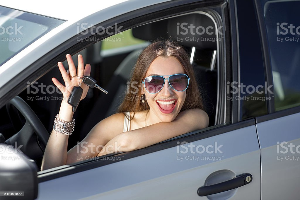 Car driver woman happy showing keys out window stock photo