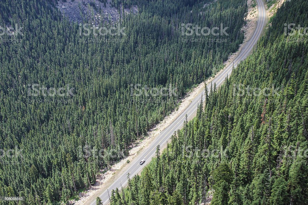 Car drives through a forest and mountain pass stock photo