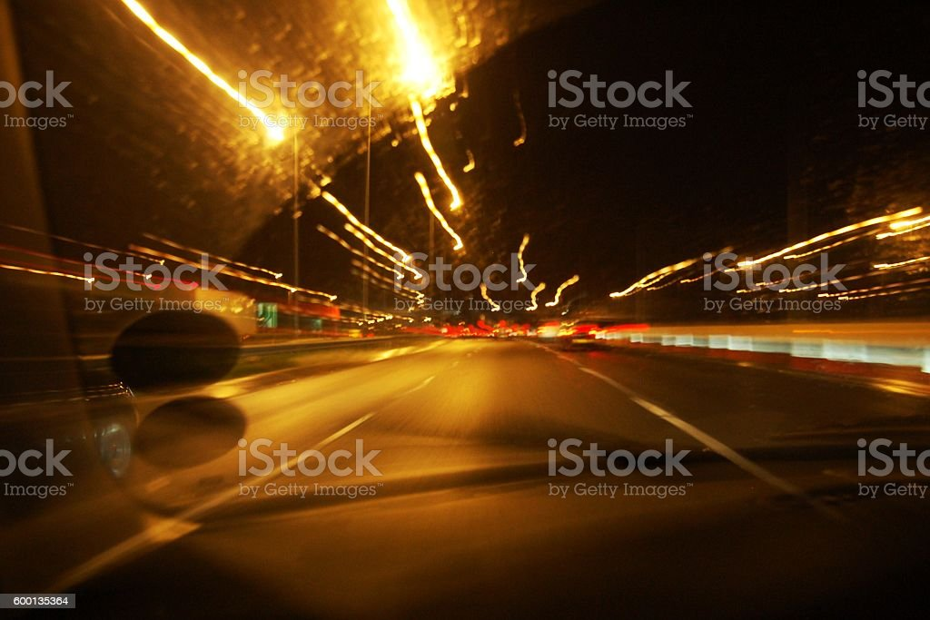 Car driving at night blurred lights. View from inside cabin. stock photo