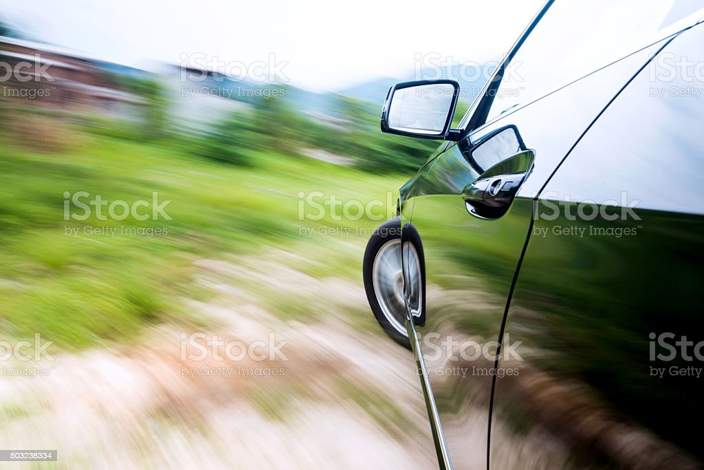 Car driving fast on country road stock photo