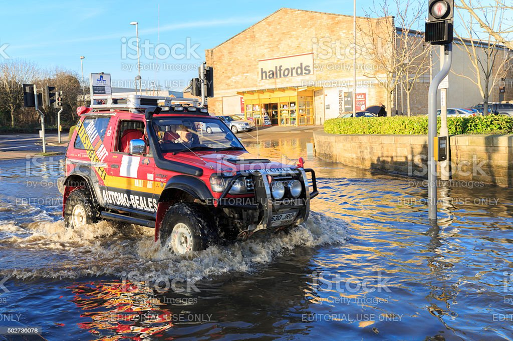 Car driving on a flooded street past shops in Leeds stock photo