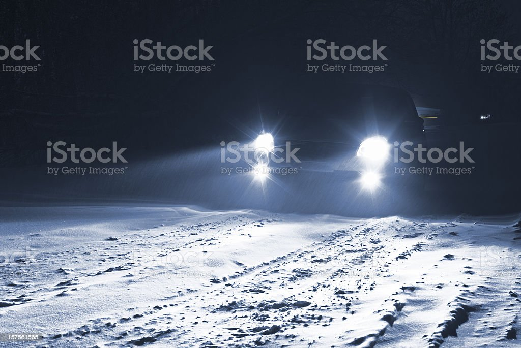 Car driving on a snowy country road in a snow storm. stock photo