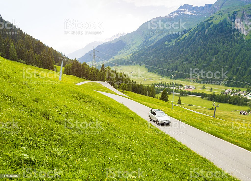 Car driving on a winding road in Swiss Alps royalty-free stock photo