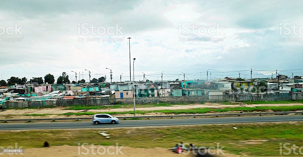 Car driving past roadside shantytown in Cape Town stock photo