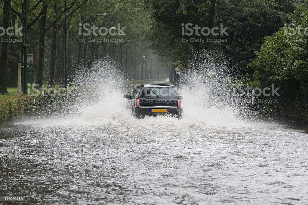 Car driving through a flooded street stock photo