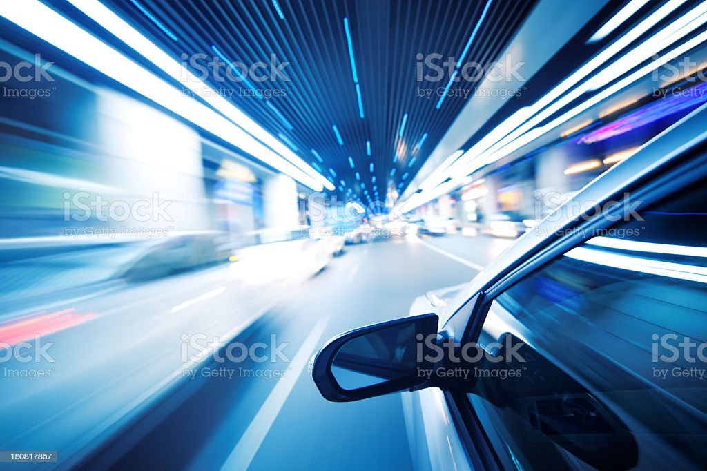 A car driving through a tunnel at night stock photo