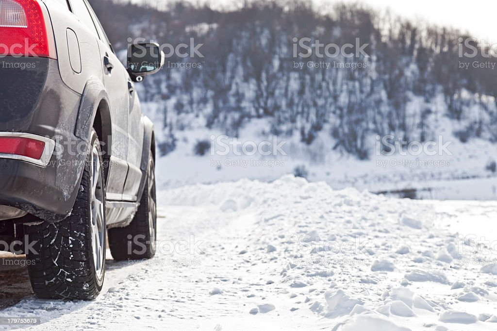 Car driving up a hill in the snow stock photo