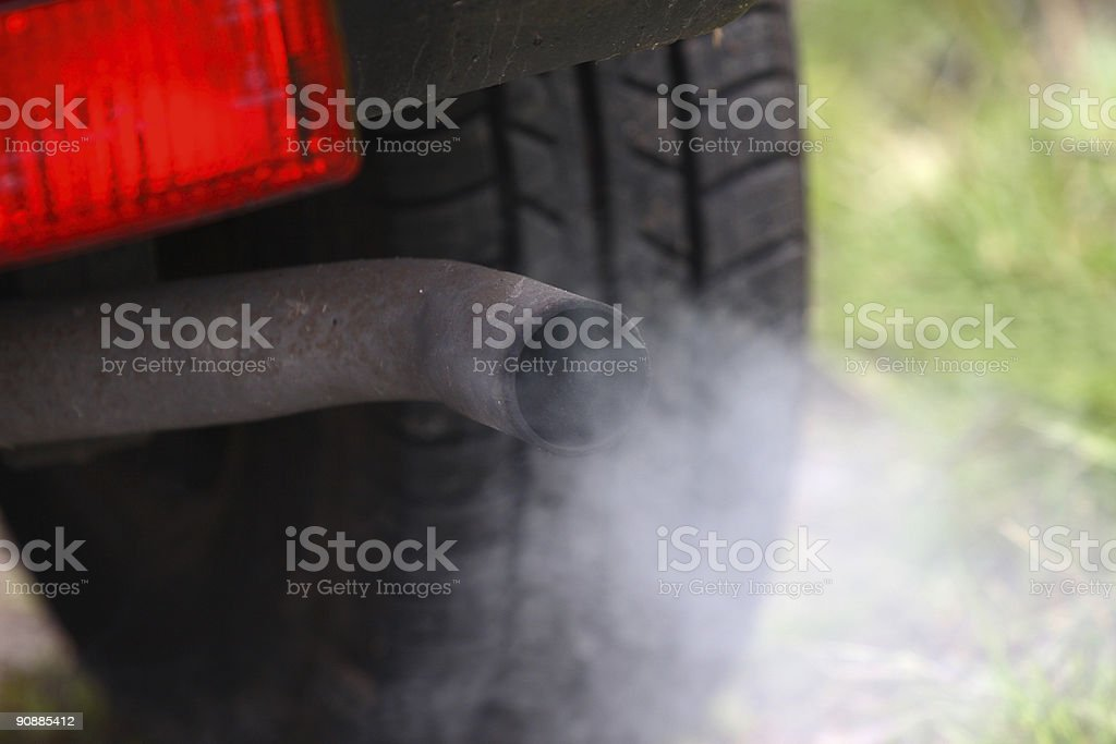 Car exhaust fumes coming from a smoking automobile rear pipe stock photo