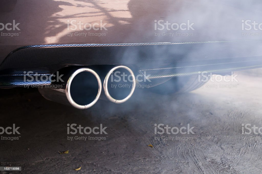 Car exhaust pipe expelling smoke stock photo