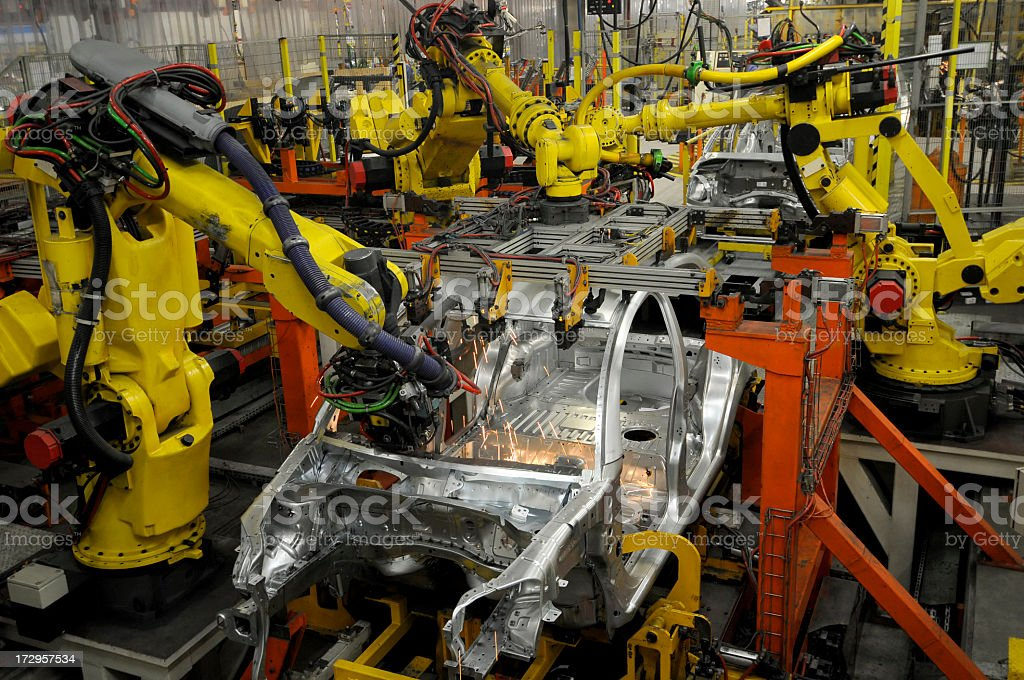 Car factory building new vehicles with robotic arms stock photo
