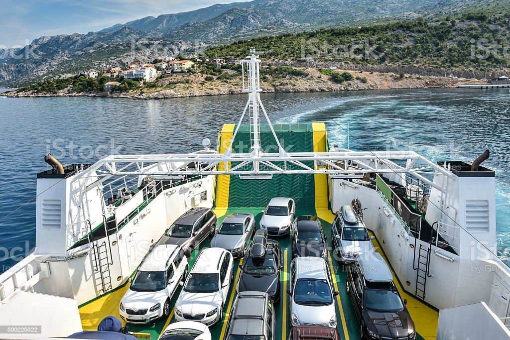 Car Ferry Boat with rows of cars is leaving port. stock photo